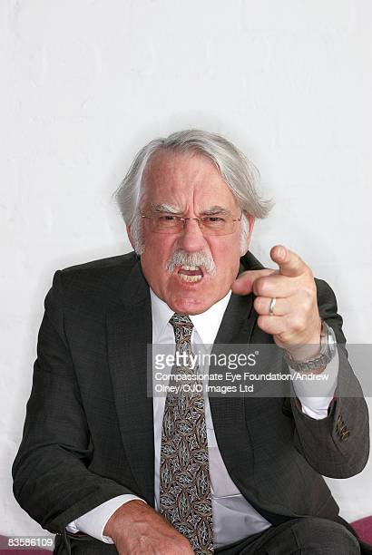 Angry senior businessman pointing to camera