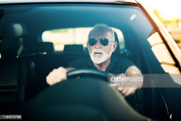 angry senior man driving a car avoiding a car accident. - avoidance stock pictures, royalty-free photos & images