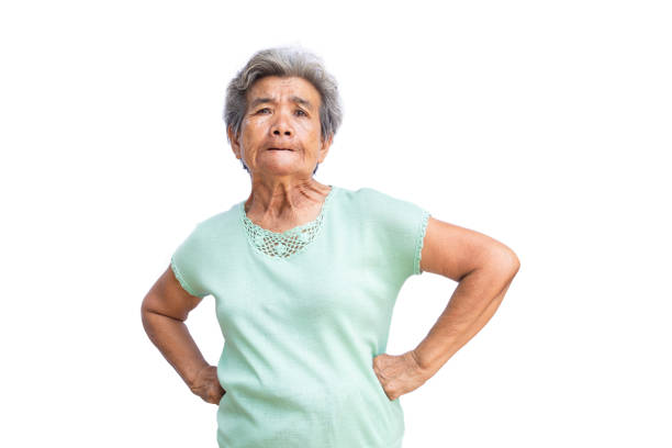 angry senior woman with hands on hip standing against white background - angry asian old woman stock pictures, royalty-free photos & images
