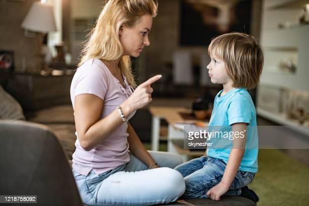 madre soltera enojada regañando a su pequeño hijo en casa. - penalty fotografías e imágenes de stock