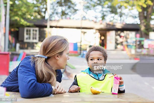 Angry teacher looking at student holding juice box outside kindergarten