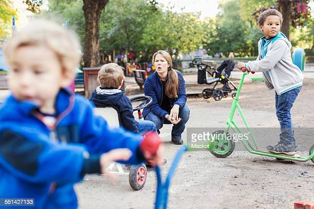 Angry teacher with children playing on playground