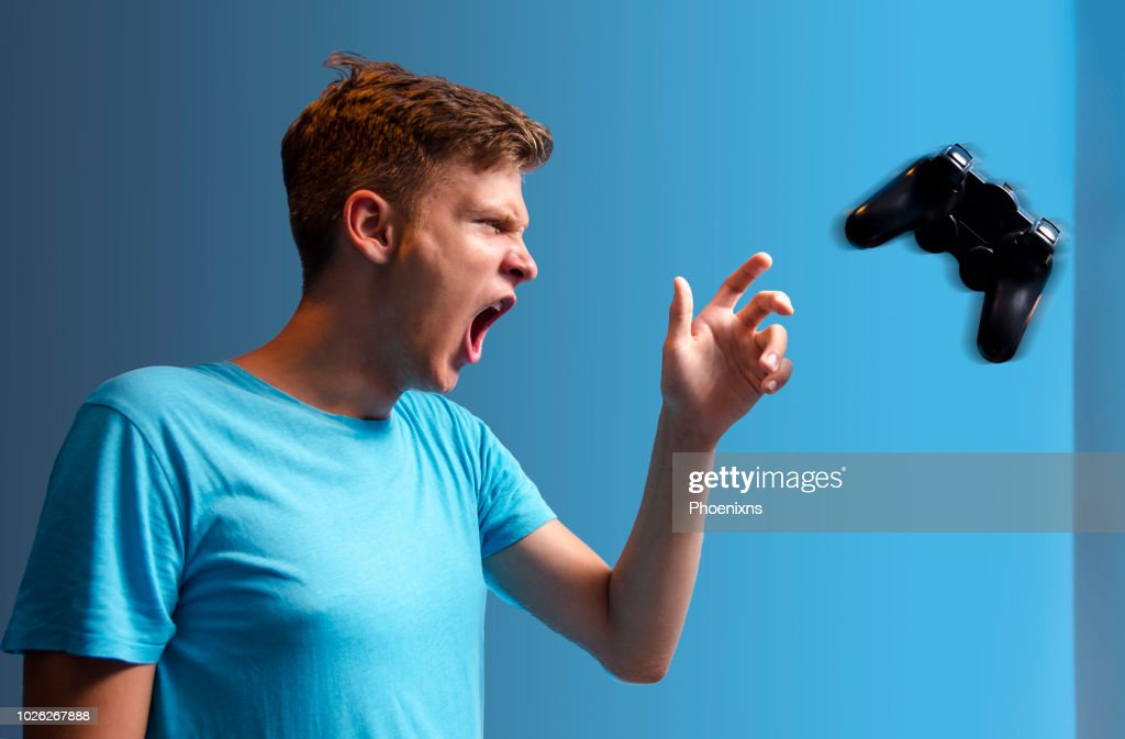 Angry teen throwing gaming controller : Stock Photo