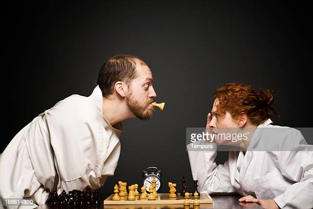 angry warden loosing chess game to loony in the mental_asylum - straight jacket stock pictures, royalty-free photos & images