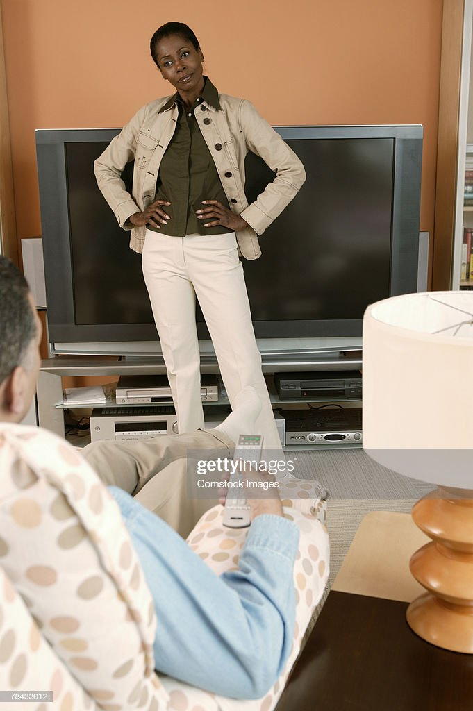 Angry woman blocking television from man : Stockfoto