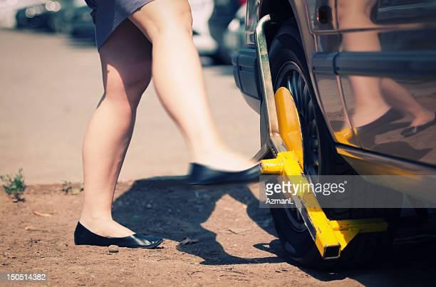 Angry woman kicks wheel lock