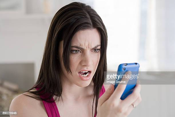 Angry woman looking at cellphone