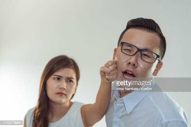 angry woman punching man standing against wall - hitting stock pictures, royalty-free photos & images