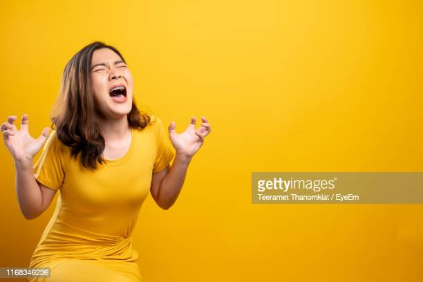 angry woman screaming against yellow background - 叫ぶ ストックフォトと画像