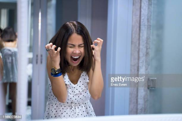 angry woman shouting at mirror and crying - insanity stock pictures, royalty-free photos & images