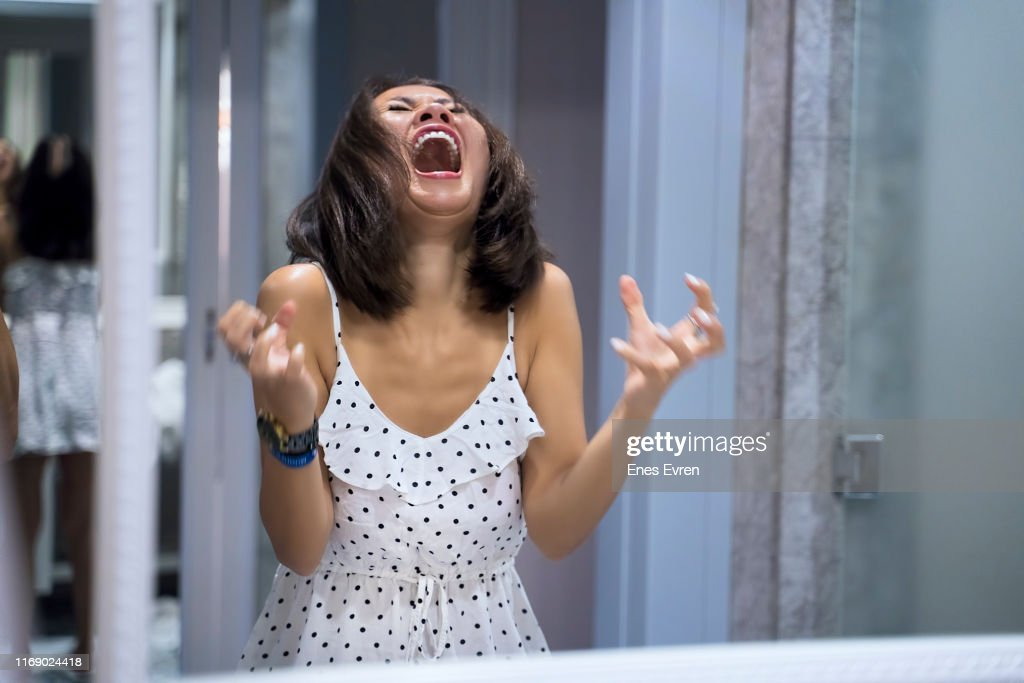 Angry woman shouting at mirror and crying : Stock Photo