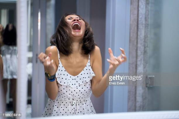 angry woman shouting at mirror and crying - shouting stock pictures, royalty-free photos & images