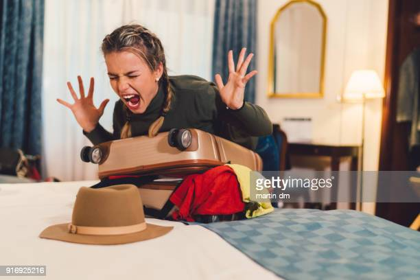 Angry woman struggling with overflowing suitcase