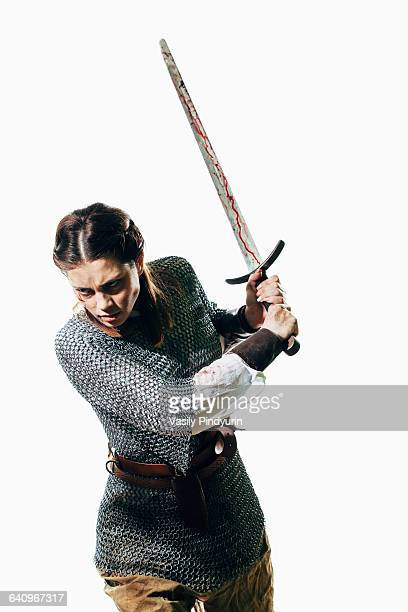 angry woman wearing chain mail holding sword against white background - mulher guerreira imagens e fotografias de stock