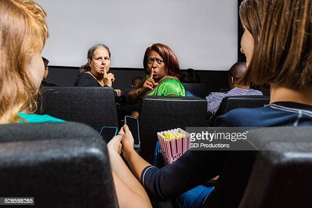 Angry women shushing teens with cell phones in movie theater