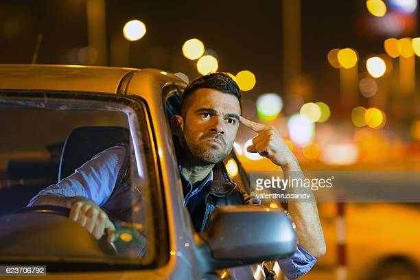 Angry young man driving car at night
