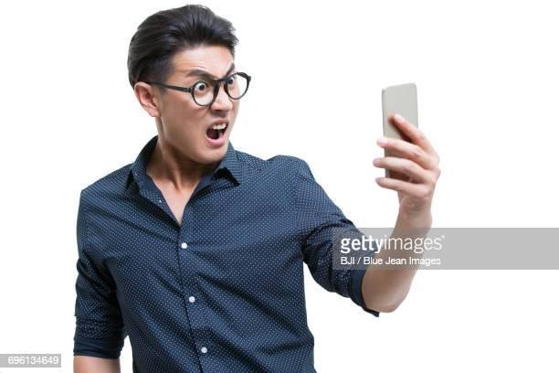 Angry young man looking at smart phone