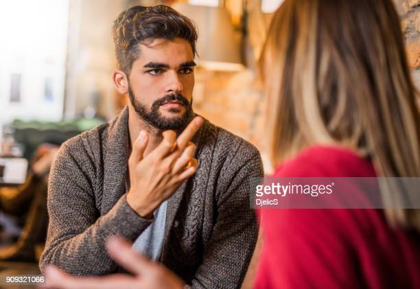 Angry young man showing a middle finger to his girlfriend.