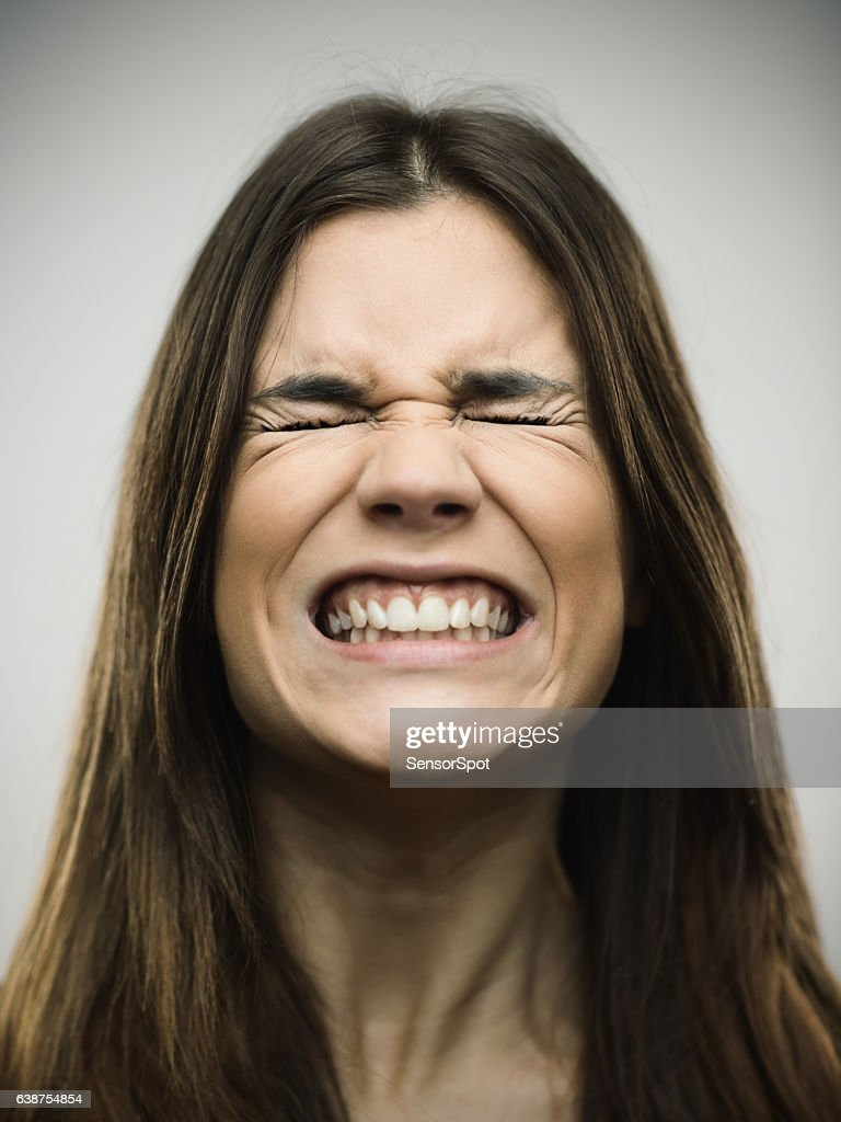 Angry young woman clenching teeth : Stock Photo