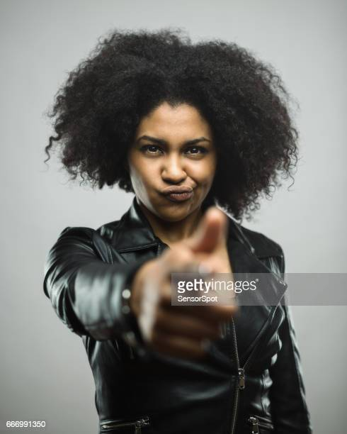 Angry young woman pointing at you