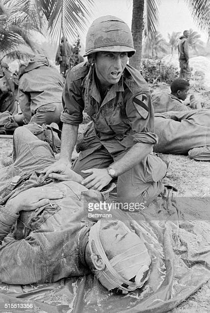 Anguish crosses the face of this busy doctor shouting for a stretcher team as he treats a wounded soldier of the US 1st Cavalry Division near Bong...
