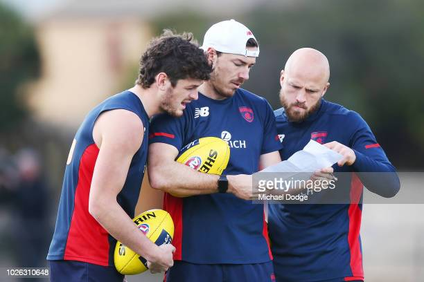 Angus Brayshaw Michael Hibberd and Nathan Jones of the Demons read paperwork during a Melbourne Demons AFL training session at Gosch's Paddock on...
