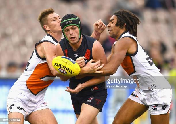Angus Brayshaw of the Demons handballs whilst being tackled by Adam Tomlinson and Aiden Bonar of the Giants during the round 23 AFL match between the...