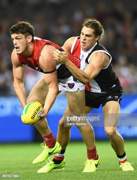 Angus Brayshaw of the Demons handballs whilst being tackled by Jack Steele of the Saints during the round one AFL match between the St Kilda Saints...