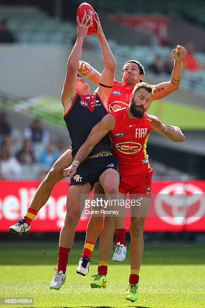 Angus Brayshaw of the Demons marks infront of Nick Malceski and Greg Broughton of the Suns during the round one AFL match between the Melbourne...