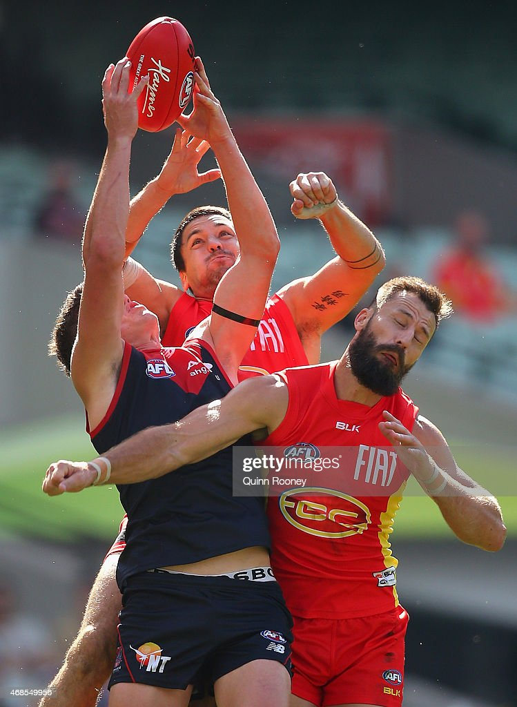 Angus Brayshaw of the Demons marks infront of Nick Malceski and Greg Broughton of the Suns during the round one AFL match between the Melbourne Demons and the Gold Coast Suns at Melbourne Cricket Ground on April 4, 2015 in Melbourne, Australia.