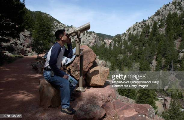 Angus Chen from Boston Mass looks at climbers and birds with a scope mounted along the Fowler Trail in Eldorado Canyon State Park last Saturday