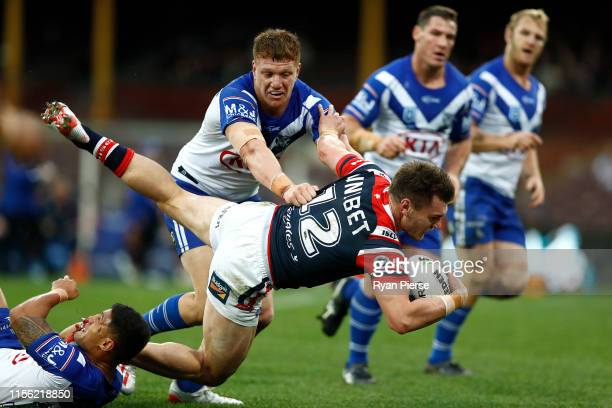 Angus Crighton of the Roosters is tackled by Dylan Napa and Fa'amanu Brown of the Bulldogs is tackled during the round 14 NRL match between the...