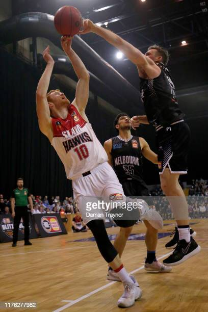 Angus Glover of the Hawks drives to the basket as Mitch McCarron of United defends during the NBL Blitz pre-season match between Melbourne United and...