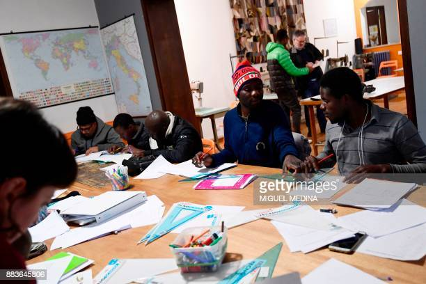 Angus MACKINNON Migrants study in a classroom at the 'LaiMomo' headquarters a vocational training programme to teach skills in leather bag making to...