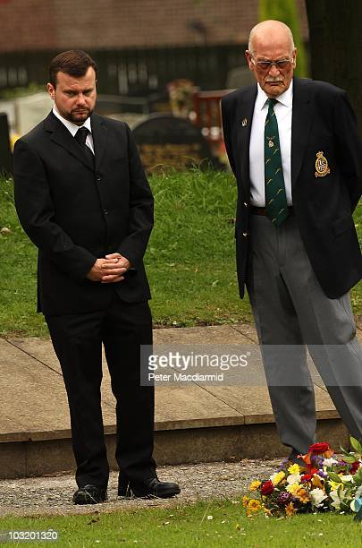 Angus Moat looks at floral tributes after the funeral of his brother Raoul Moat as his uncle Charlie Alexander looks on at West Road Crematorium on...