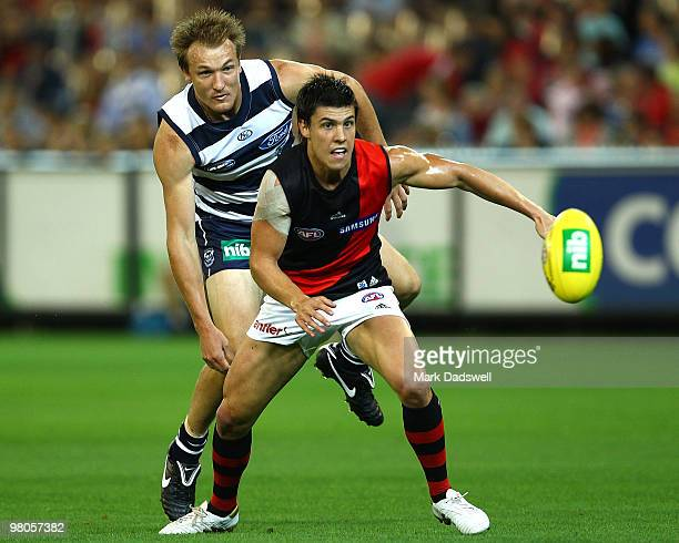 Angus Monfries of the Bombers competes with Darren Milburn of the Cats during the round one AFL match between the Geelong Cats and the Essendon...
