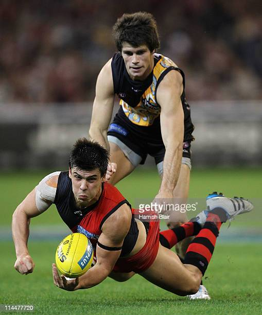 Angus Monfries of the Bombers handpasses as he is tackled by Trent Cotchin of the Tigers during the round nine AFL match between the Richmond Tigers...