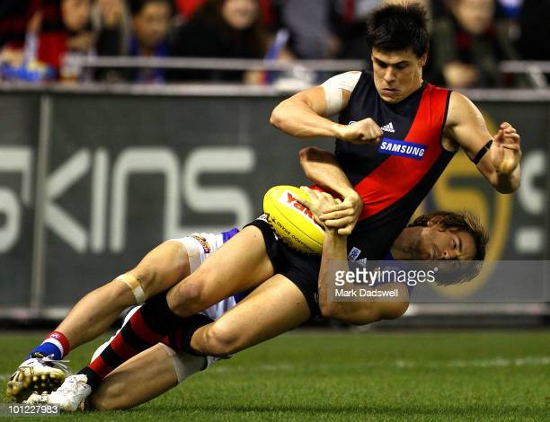 Angus Monfries of the Bombers is wrapped up in a tackle by Dylan Addison of the Bulldogs during the round 10 AFL match between the Essendon Bombers...