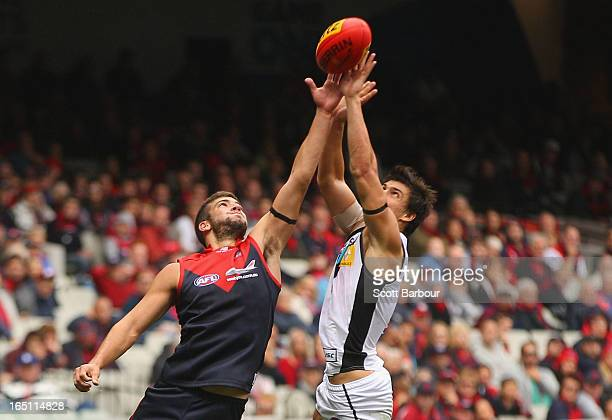 Angus Monfries of the Power and Jimmy Toumpas of the Demons compete for the ball during the round one AFL match between the Melbourne Demons and Port...