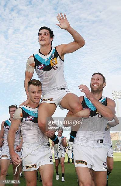 Angus Monfries of the Power is hoisted up by Robbie Gray and Jay Schulz after winning in his 200th game during the round nine AFL match between the...