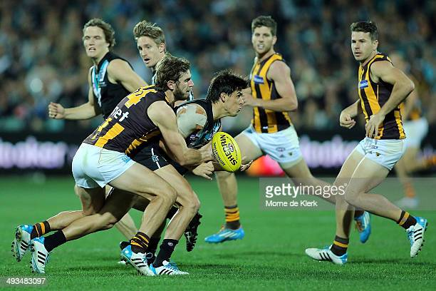 Angus Monfries of the Power is tackled by Grant Birchall of the Hawks during the round 10 AFL match between the Port Adelaide Power and the Hawthorn...