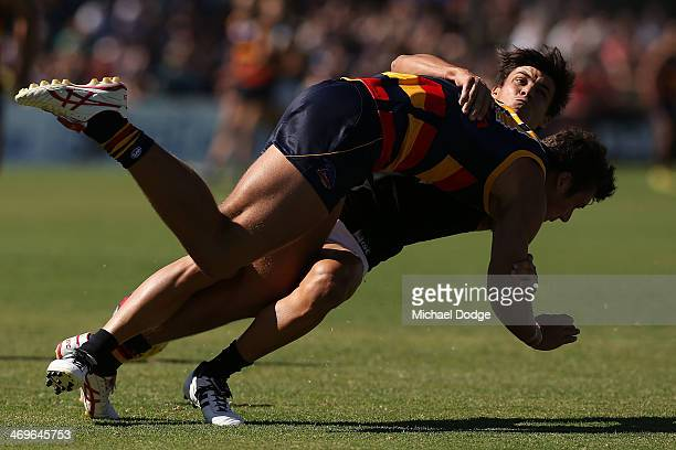 Angus Monfries of the Power tackles Kyle Hartigan of the Crows during the round two AFL NAB Challenge Cup match between the Adelaide Crows and the...