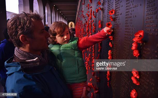 Angus White watches as his daughter Scarlett puts a poppy in beside her great grandfathers after the dawn service at the Australian War Memorial on...