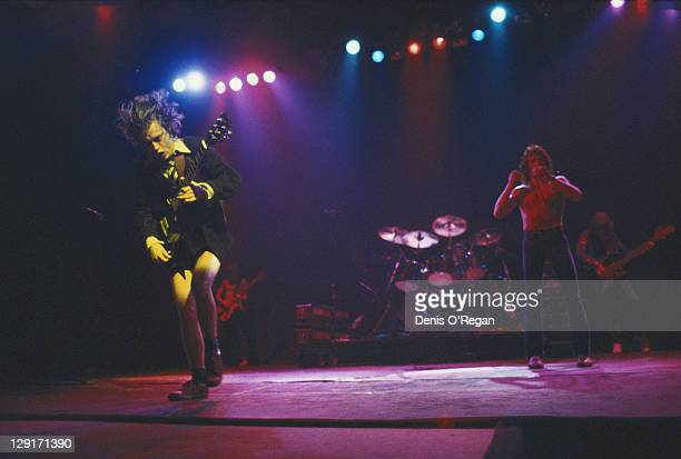 Angus Young and Bon Scott performing with rock group AC/DC circa 1976