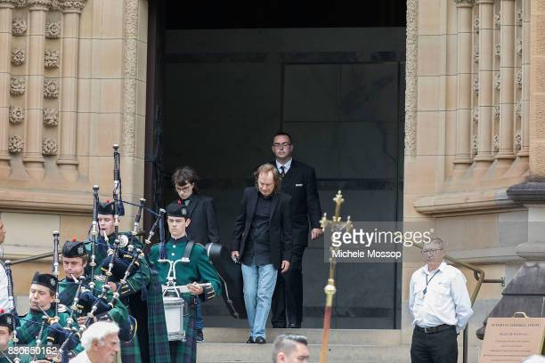 Angus Young and Ross Young son of Malcolm follow his brother's coffin out carrying his guitar The funeral service for AC/DC cofounder Malcolm Young...