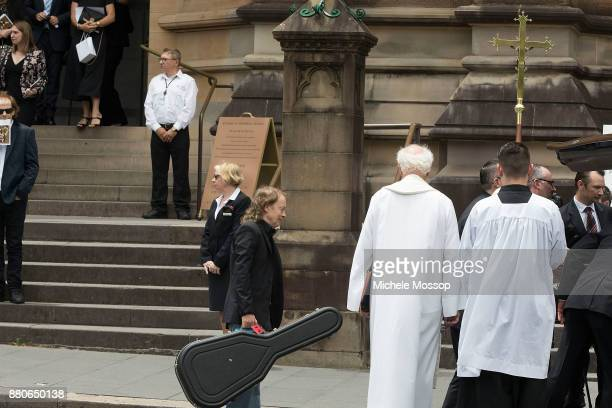 Angus Young follows his brother's coffin out carrying his guitar at the funeral service for AC/DC cofounder Malcolm Young at St Mary's Cathedral on...
