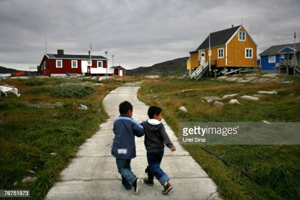 Angut Rasbach a fiveyearold Inuit fisherman's son and his fouryearold cousin Nikki Lange run August 26 2007 in their home village of Ilimanaq...