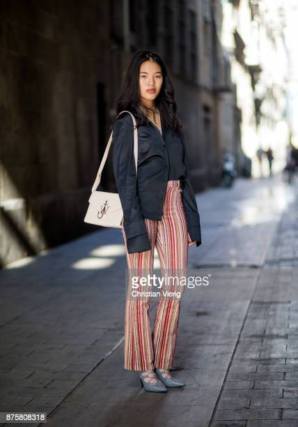 Anh Dinh wearing striped vintage flared pants black Mango button shirt with wide sleeves JW Anderson bag grey heels on November 18 2017 in Barcelona...