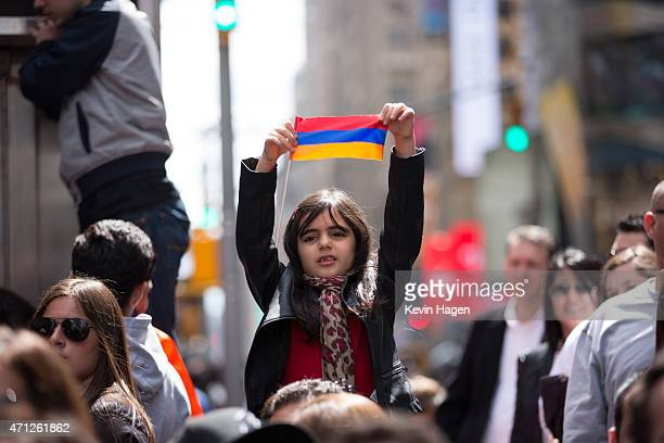 Ani Avagyan holds a flag during a rally to commemorate the 1915 Turkish massacre of Armenians in Times Square April 26 2015 in New York City The...