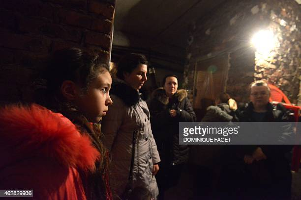 Ania 11yearsold and residents wait for the end of the shelling in Donetsk's Petrovski district in the eastern Ukraine on February 4 2015 Donetsk's...